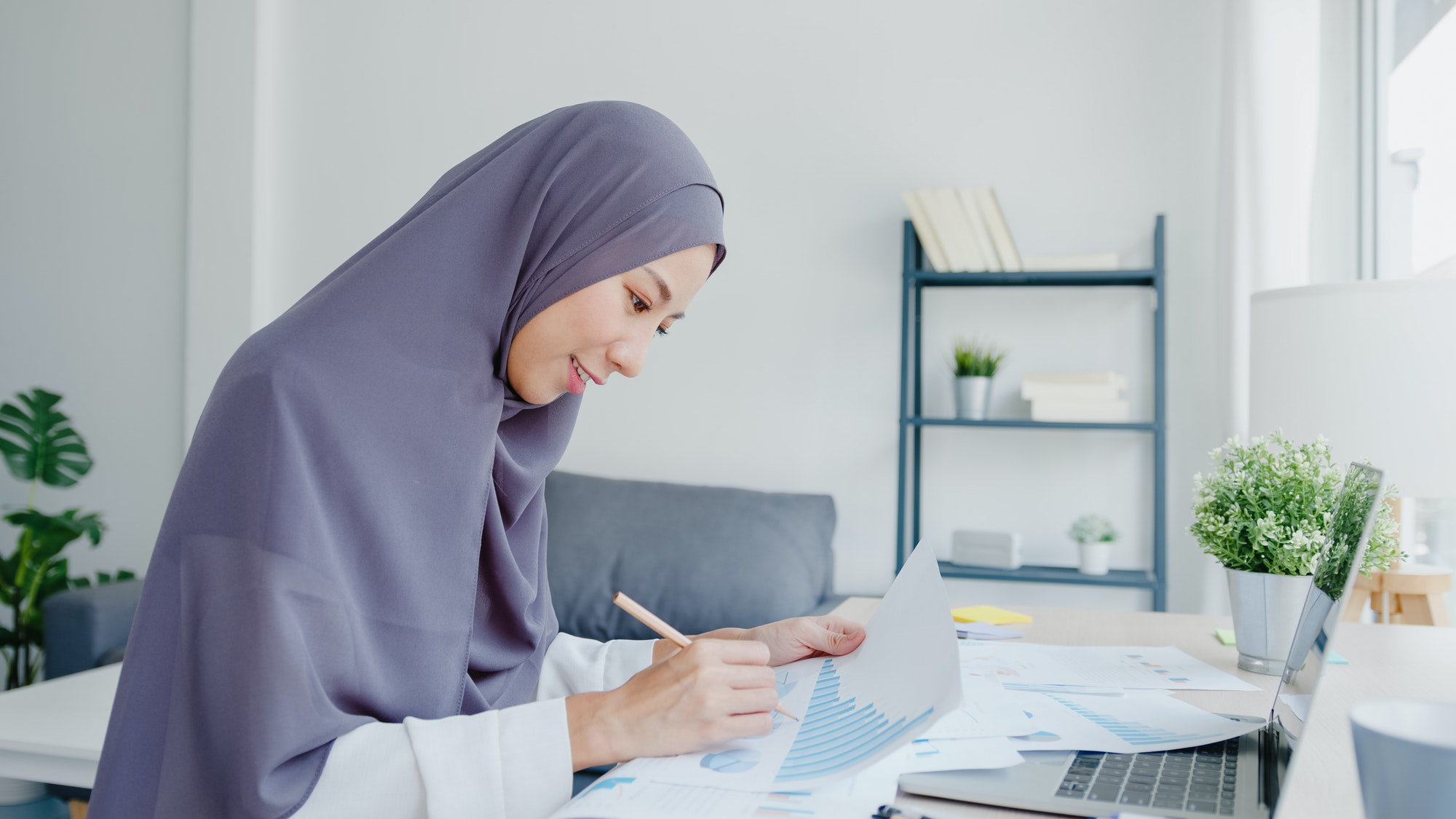 Beautiful Asia muslim lady in headscarf using laptop in living room at house.